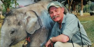 Craig Sholley of African Wildlife Foundation sitting with a baby elephant