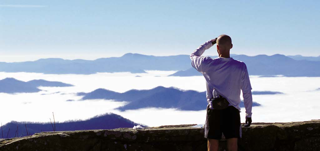 Man standing with his hand shielding his eyes overlooking misty mountains